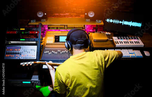 back of male asian musician recording guitar sound in home studio. music production concept - 254354731