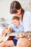 Junge lernt erste Griffe auf der Gitarre
