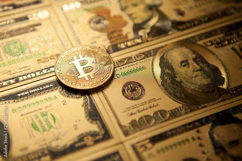 Leinwanddruck Bild Bitcoin golden coin cryptocurrency on golden US dollar.