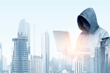 Double exposure of hacker in black hoodie holding laptop and modern city