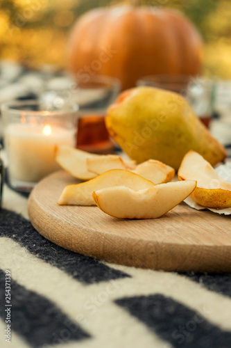 Picnic in autumn park with pear, pumpkin and candles. Warm sunny weather. Space for text © AnnaDemy