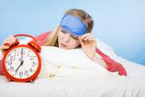Sleeping woman wearing pajamas holding clock