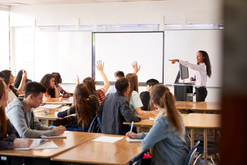 Female High School Teacher Asking Question Standing By Interactive Whiteboard Teaching Lesson