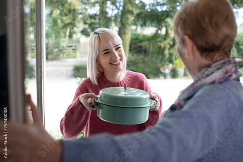 Leinwanddruck Bild Woman Bringing Meal For Elderly Neighbour