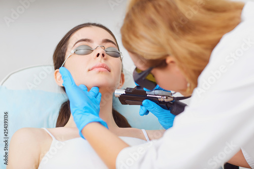 Laser hair removal on the face of a young woman in a cosmetology