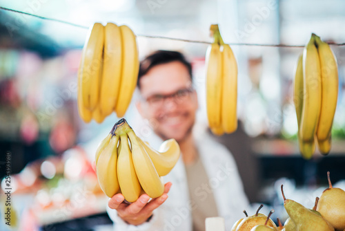 Selling bananas at farmer's market. - 254393980