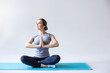 Leinwandbild Motiv Sports woman in the lotus position on the blue yoga mat on a gray background.