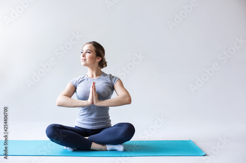 Leinwanddruck Bild Sports woman in the lotus position on the blue yoga mat on a gray background.