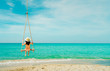 Asian woman wear swimwear and hat swing the swings at sand beach  and looking beautiful tropical paradise sea and sky on sunny day. Summer vacation. Summer vibes. Enjoying and relaxing girl on holiday