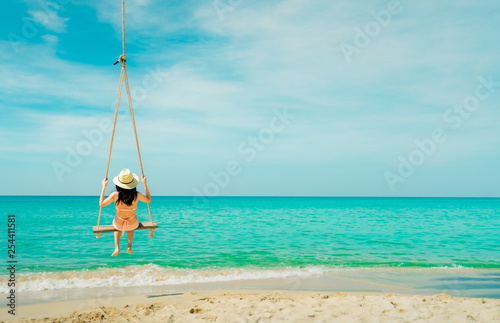 Leinwanddruck Bild Asian woman wear swimwear and hat swing the swings at sand beach  and looking beautiful tropical paradise sea and sky on sunny day. Summer vacation. Summer vibes. Enjoying and relaxing girl on holiday