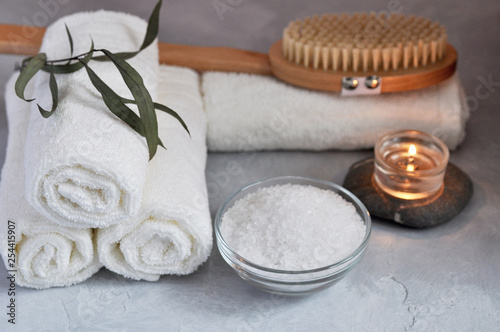 Close up view of Spa relax concept. White Terry towels, stones, candle, sea salt and wooden massage brush on a gray textured background. - 254415907