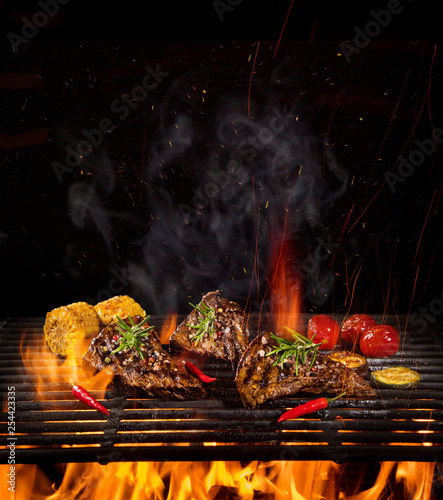 Tasty Beef steaks on iron cast grate with fire flames. - 254423335