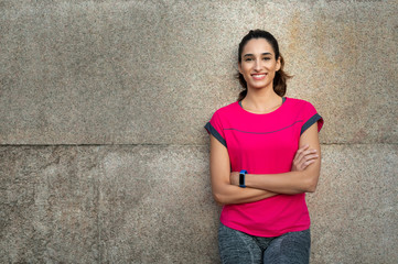 Sporty woman leaning against wall