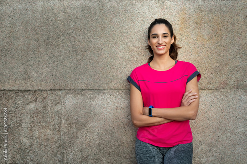 Fototapeten Fitness Sporty woman leaning against wall