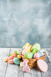Leinwanddruck Bild - Easter greeting card background with pastel colored eggs and homemade cookies shaped in eggs and bunnies rabbits. With a basket, tulips, rustic wooden table, copy space top view banner