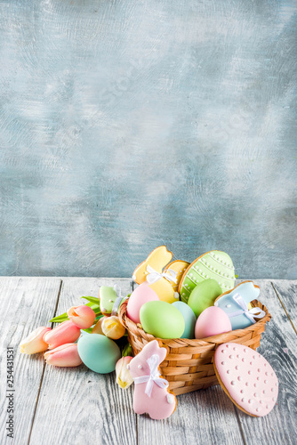 Leinwanddruck Bild Easter greeting card background with pastel colored eggs and homemade cookies shaped in eggs and bunnies rabbits. With a basket, tulips, rustic wooden table, copy space top view banner