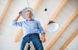 A senior man furnishing new house, having fun. New home concept.