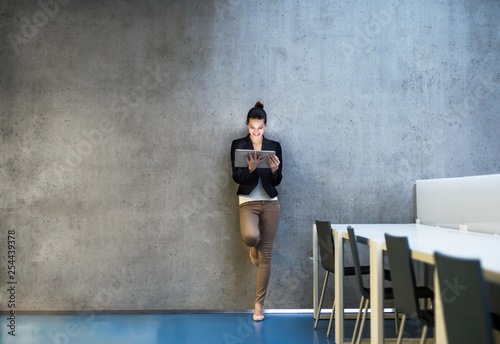 Young business woman with tablet standing against concrete wall in office.