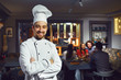 A male cook is smiling against the background of a restaurant. - 254443117