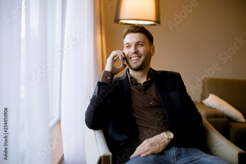 Young man using mobile phone in the room by window
