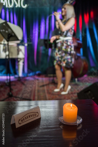 A in a music club in front of a blurred stage with a burning candle and a reserved sign.
