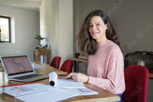 Leinwanddruck Bild Smiling lady interior designer working in home office