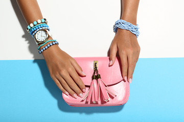 Female hands with bracelets and pink handbag on colorful background