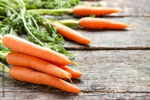 Leinwanddruck Bild Fresh carrot on grey wooden table