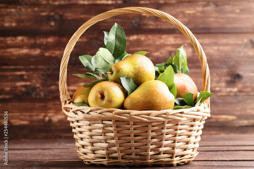 Ripe pears and green leafs in basket on brown wooden table