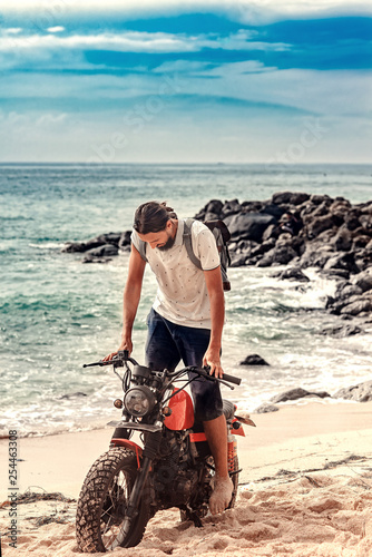 travel man in casual clothes posing on the hard red motorcycle on the awesome background of tropical beach in Bali