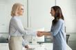 Leinwanddruck Bild - Happy young intern get hired rewarded handshaking female old boss