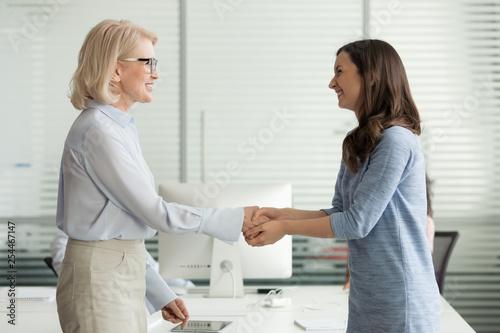 Leinwanddruck Bild Happy young intern get hired rewarded handshaking female old boss