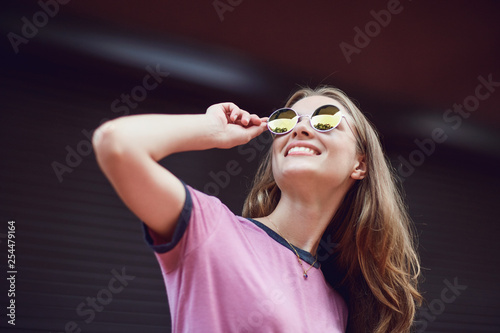 Blond girl in sunglasses smiling on a striped  background.