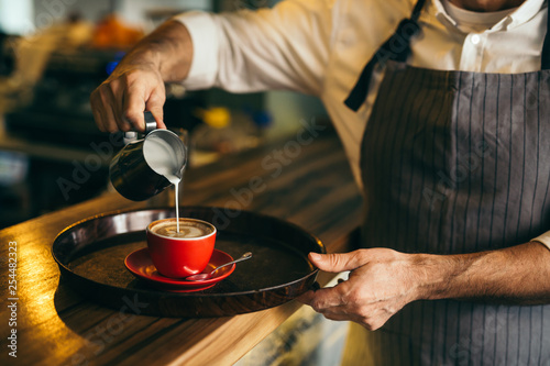 closeup of barman preparing espresso coffee. pouring milk into coffee - 254482323