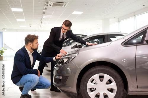 Customer and salesman choose a car in the showroom