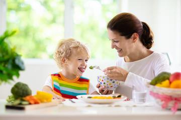 Mother feeding child. Mom feeds kid vegetables
