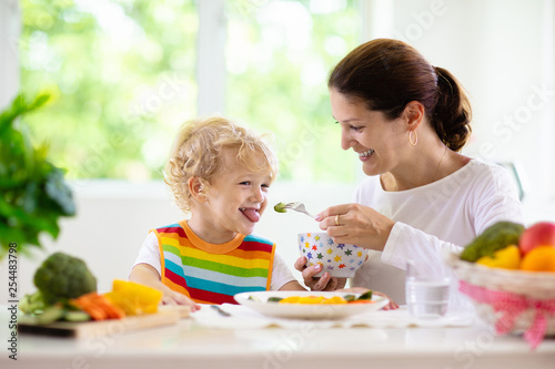 Mother feeding child. Mom feeds kid vegetables