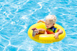 Leinwanddruck Bild - Child in swimming pool on toy ring. Kids swim.