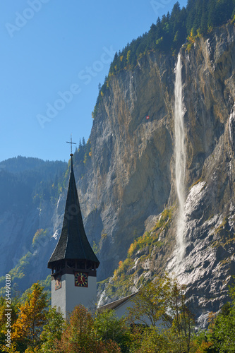 View of Staubbach waterfall with church tower at foreground  in Lauterbrunnen village in Switzerland. - 254490319