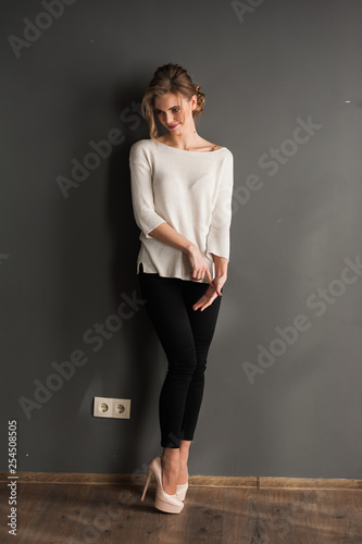 Beautiful woman wearing casual standing near grey wall