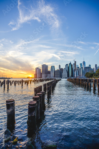 Lower Manhattan skyline scenic view from Brooklyn Bridge Park in New York City during sunset, East River side