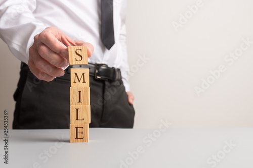 canvas print picture Businessman stacking wooden cubes to spell the word Smile