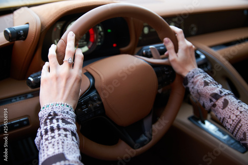 Woman driving yellow sports car with hand hold steering wheel - 254536934