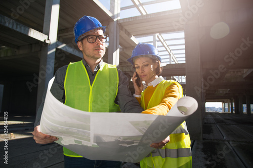 Two young engineers on a construction site, discussing project details