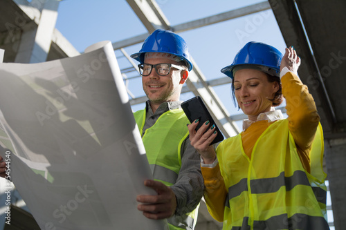 Female architect smiling and holding her helmet