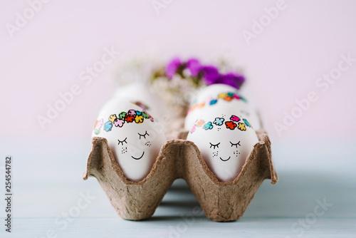 Leinwanddruck Bild Niedlich bemalte Ostereier im Eierkarton - süße Ostergrüße