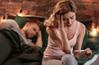 Young wife feeling worried after pregnancy test while husband sleeping