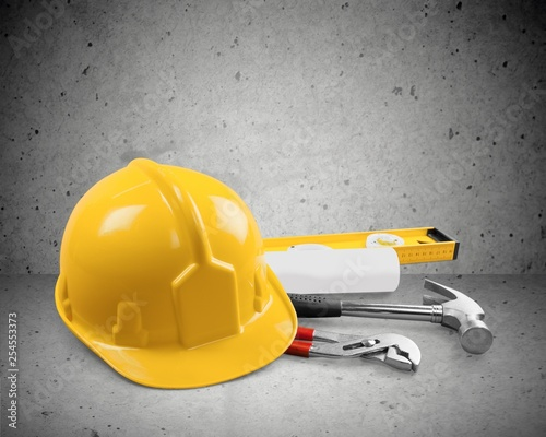 Foto Murales Yellow working hard hat, goggles and work boots on  background