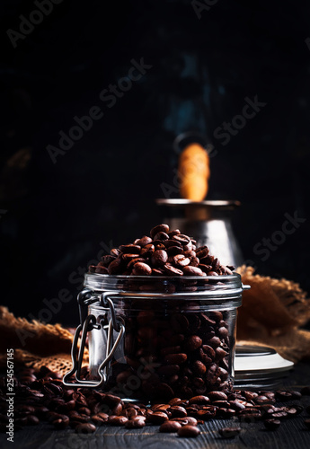 Coffee beans in a glass jar, black background, selective focus