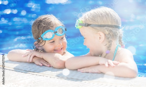 Leinwanddruck Bild Children playing in pool. Two little girls having fun in the pool. Summer holidays and vacation concept